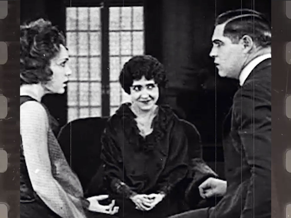Image from vintage film of woman watching two people come to a realization represents Novalda's coach mentor programs.